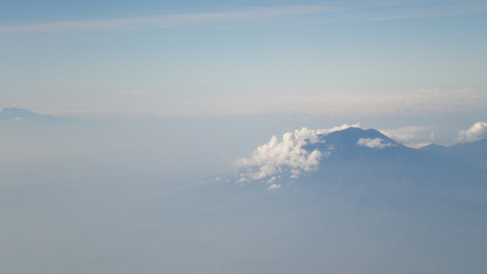 Volcanoes above the clouds over Java. By Annee Lawrence