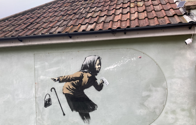 Photo of BANKSY artwork on a Bristol house showing an old woman sneezing so violently that her false teeth have shot out.