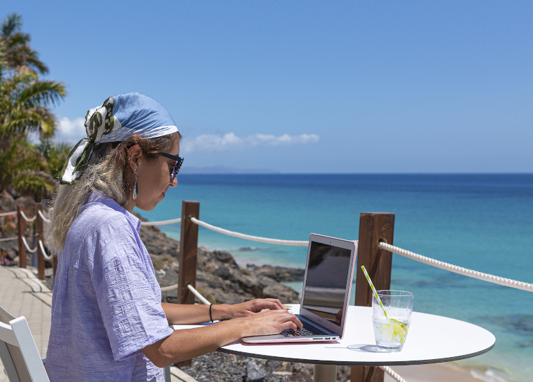 WFH From The Canary Islands. Shows woman working on a laptop with tropical beach and blue sea and sky beyond.