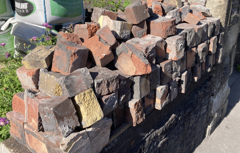 Deconstructed Wall by Judy Darley. Shows a pile of red bricks.
