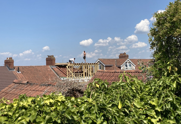 Roofers by Judy Darley. Shows two people seen over a hedge on a rooftop against a bright blue sky.
