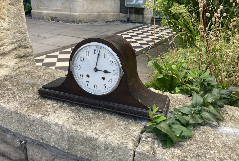 Forever 3pm by Judy Darley. Shows an old carriage clock on a garden wall.