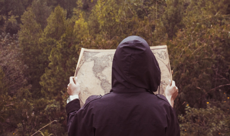 Photo by Muhammad Haikal Sjukri on Unsplash. Shows a person holding a map in front of a wildnerness.